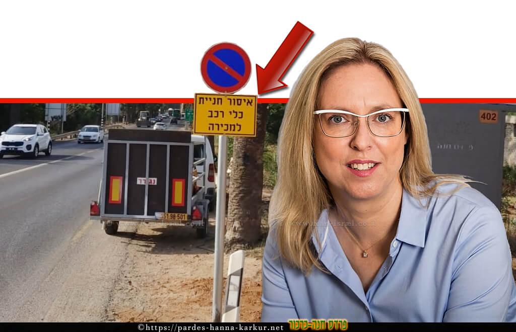 הגר פרי יגור ראש מועצת פרדס חנה-כרכור ברקע תמרור 'איסור חניית כלי רכב למכירה'